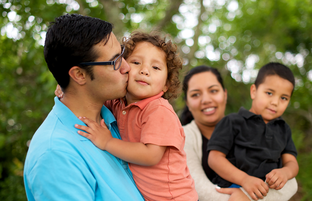 family life father kissing his son with wife and other child looking on