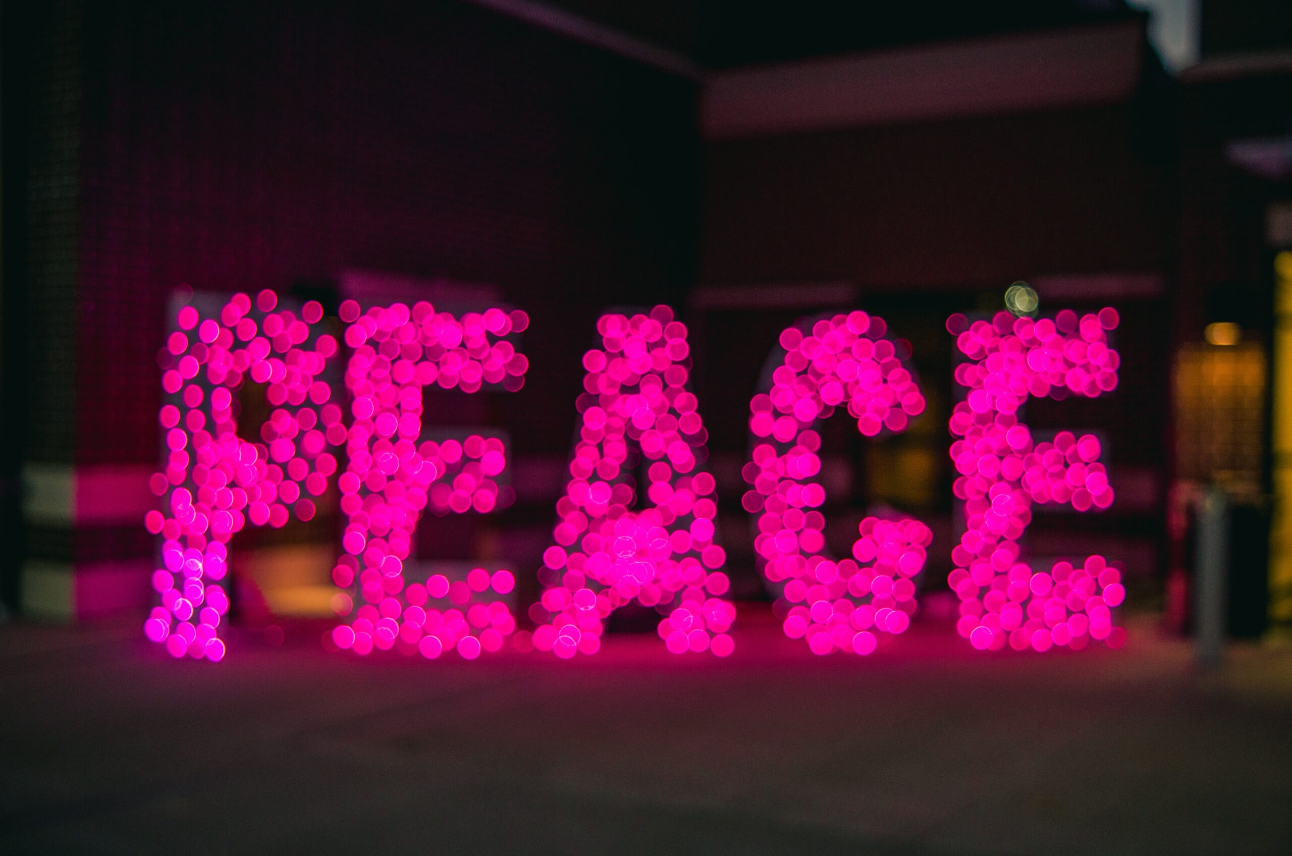 the word peace in pink lights