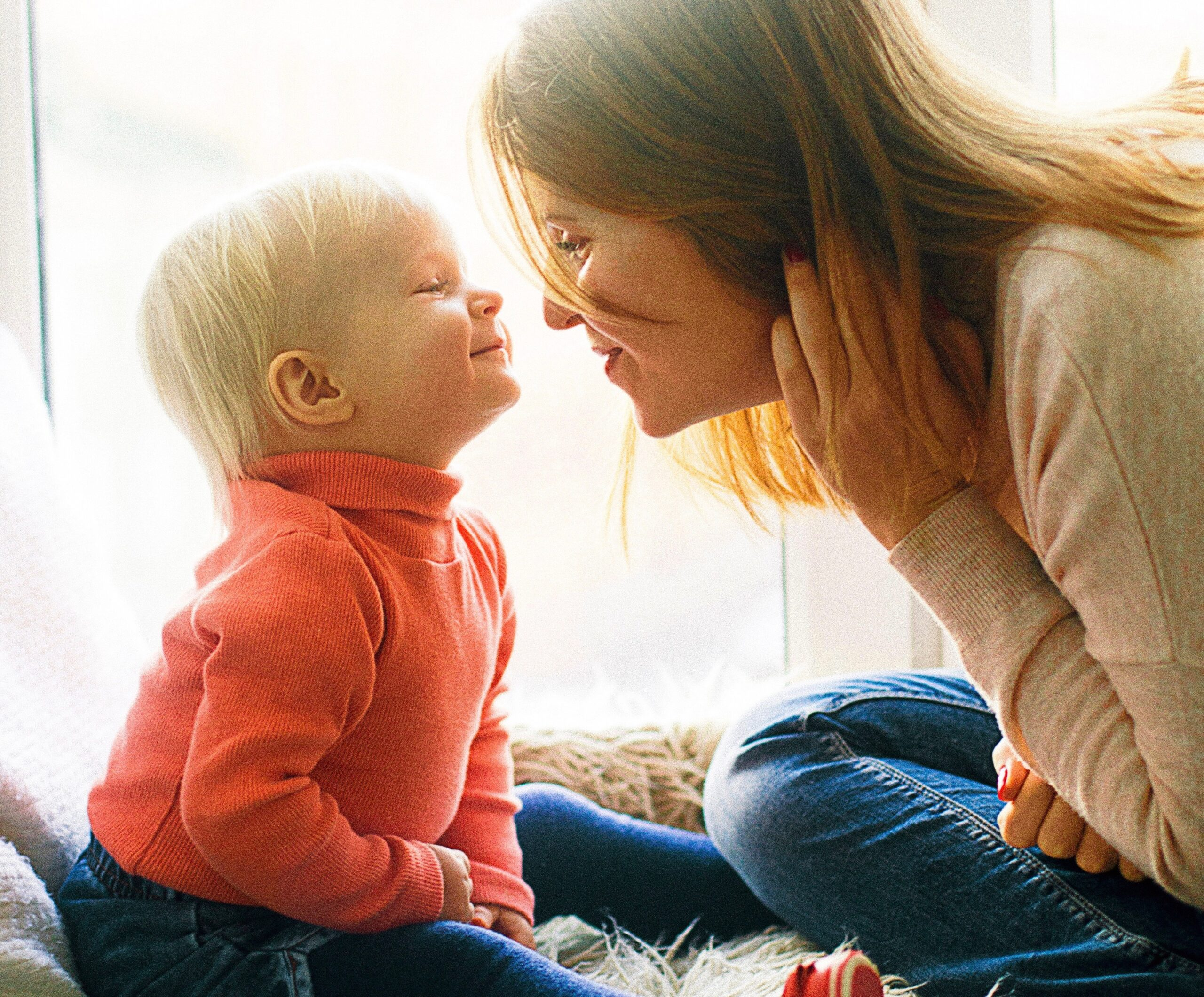 woman and child sitting on fur covered bed in front of window nose to nose with smiles