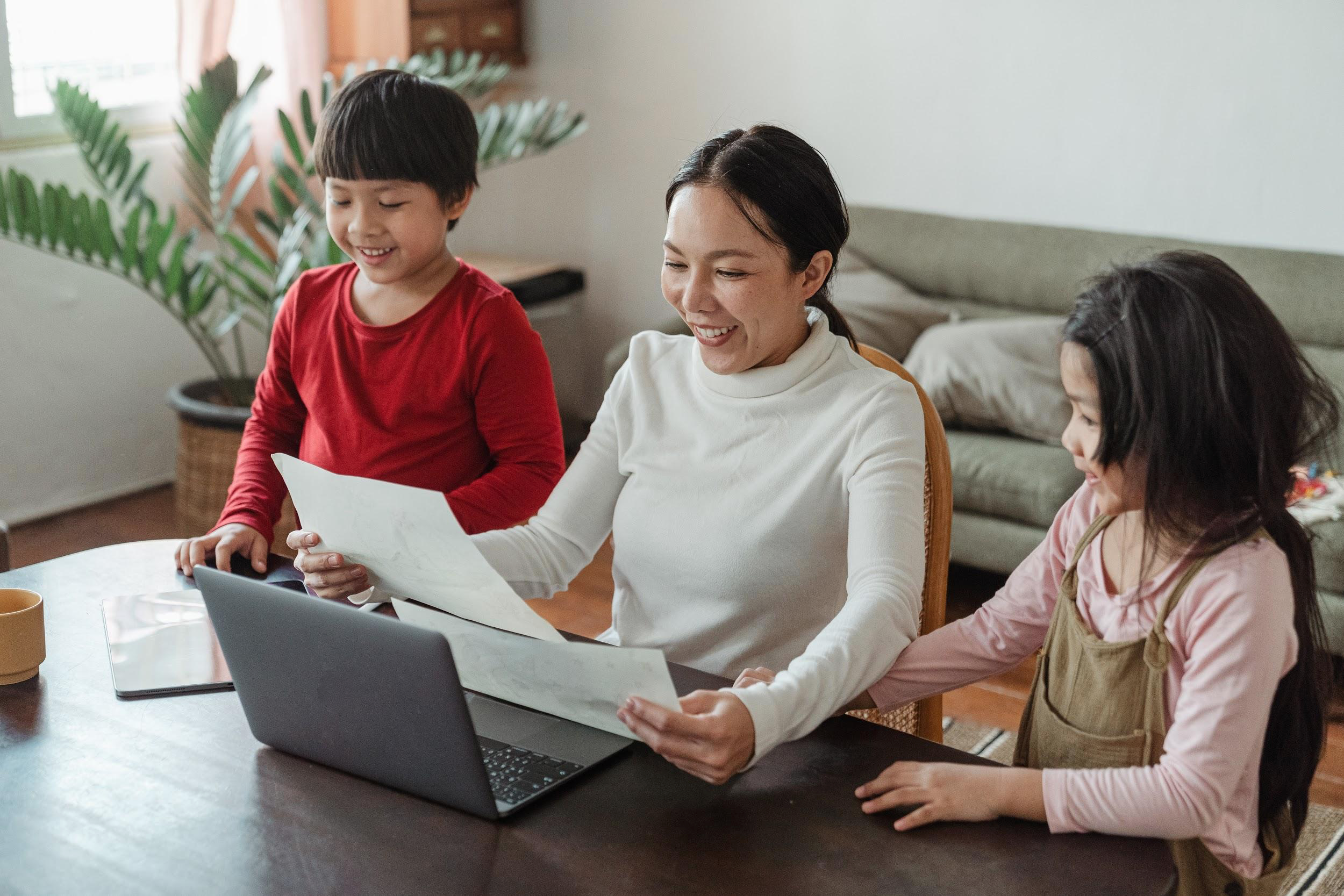 smiling working mom with boy and girl at desk in home