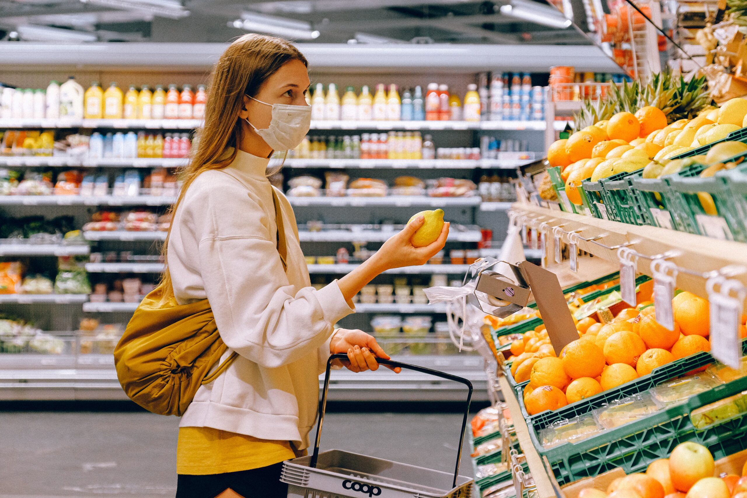 woman with white jacket wearing a mask in the produce section of the grocery store