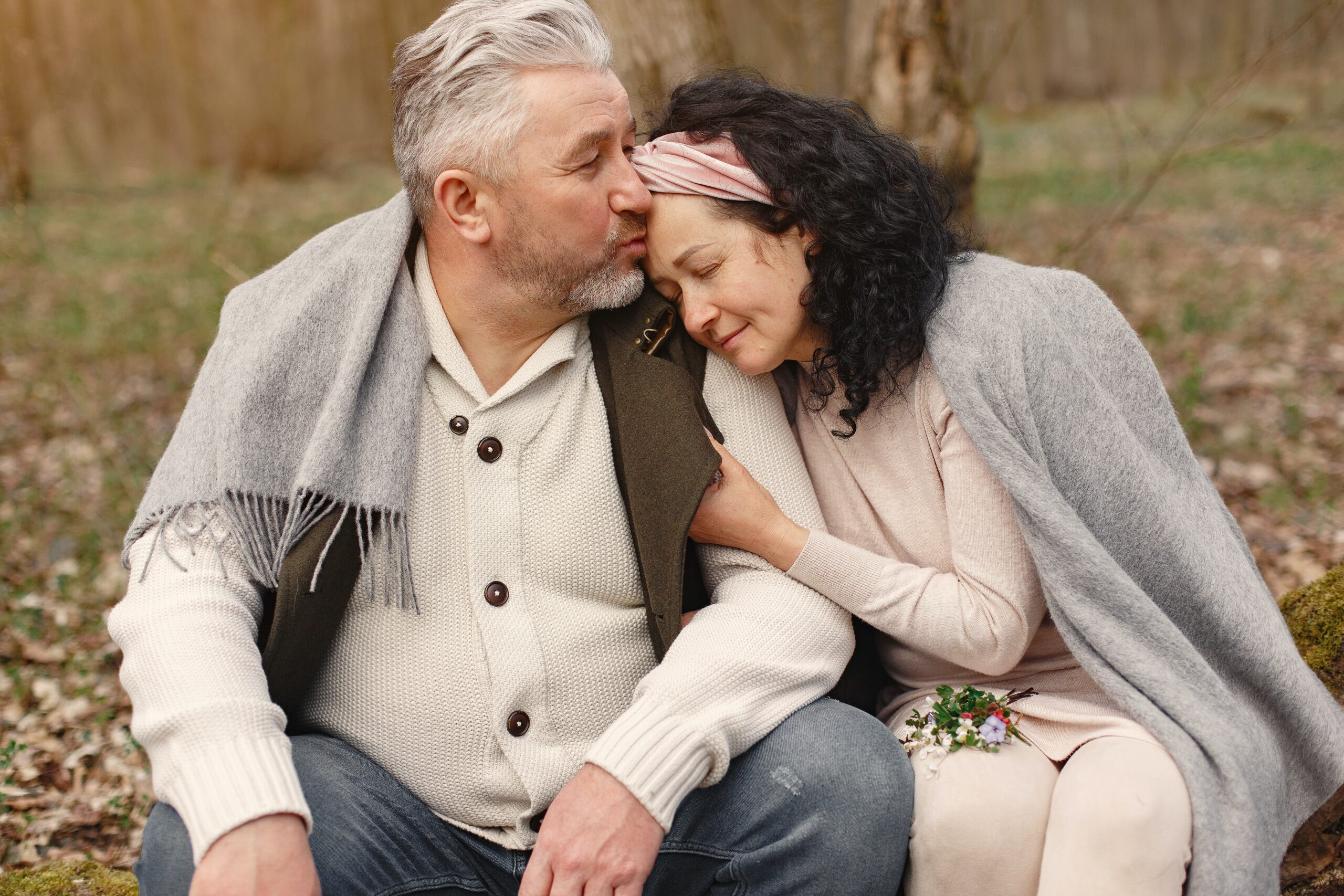 older man kissing forehead of older woman with pink headband and dark hair, who has a bit of picked flowers on her lap.