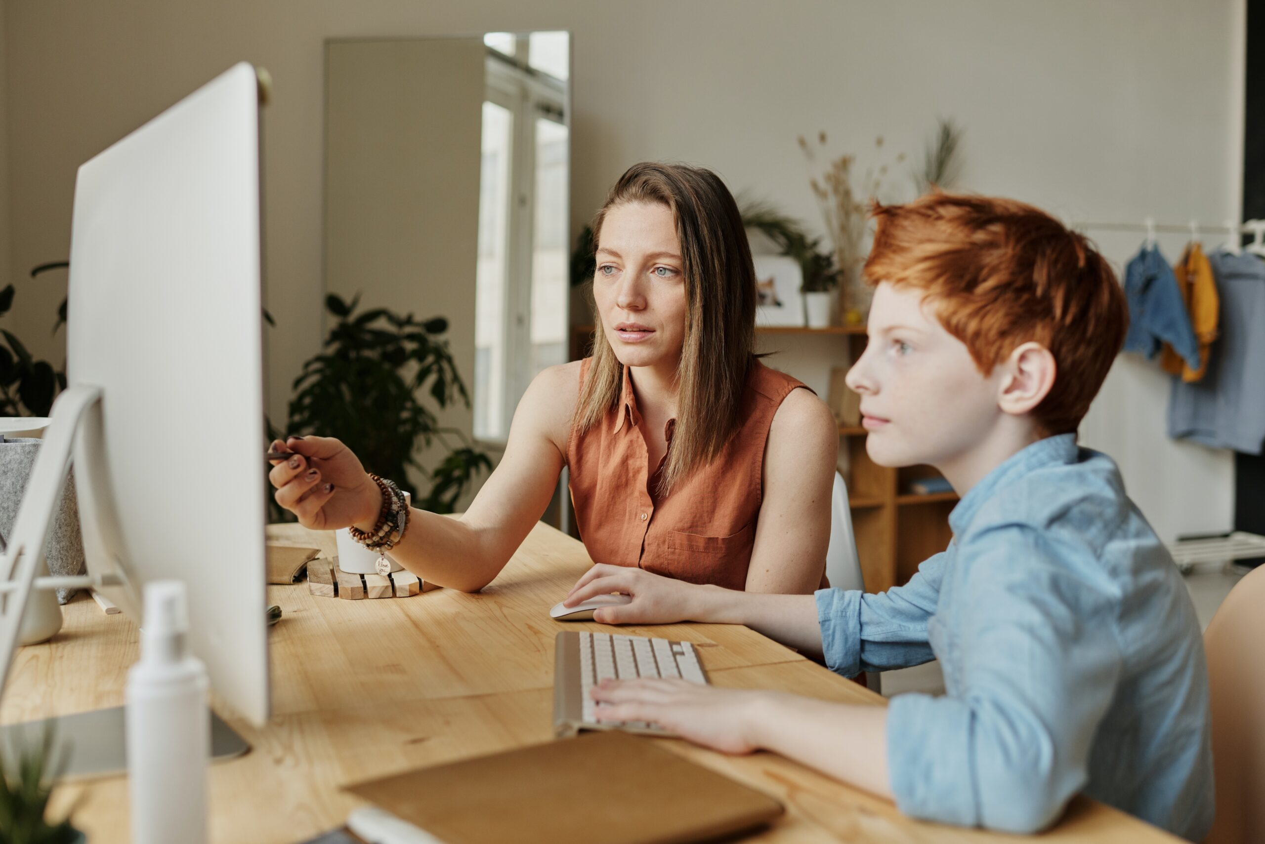 woman in orange shirt and red headed boy in blue shirt watching computer at desk in open room