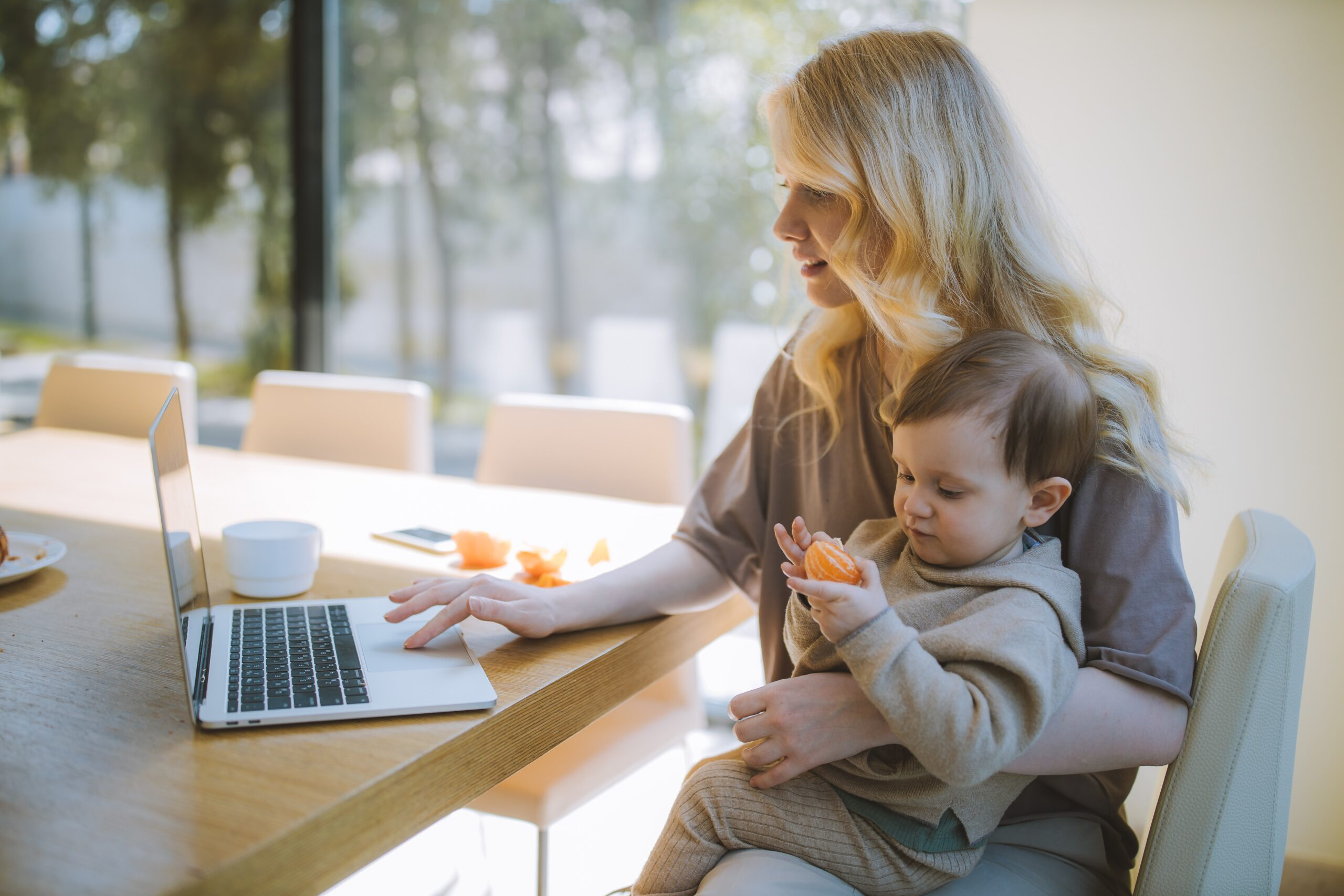 happy mom with toddler on lap. the toddler is eating an orange fruit and the woman is smiling