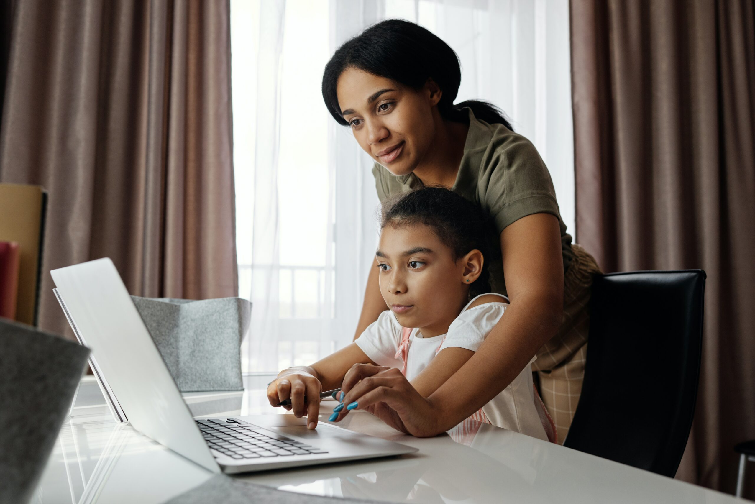 mom leaning over youth at computer