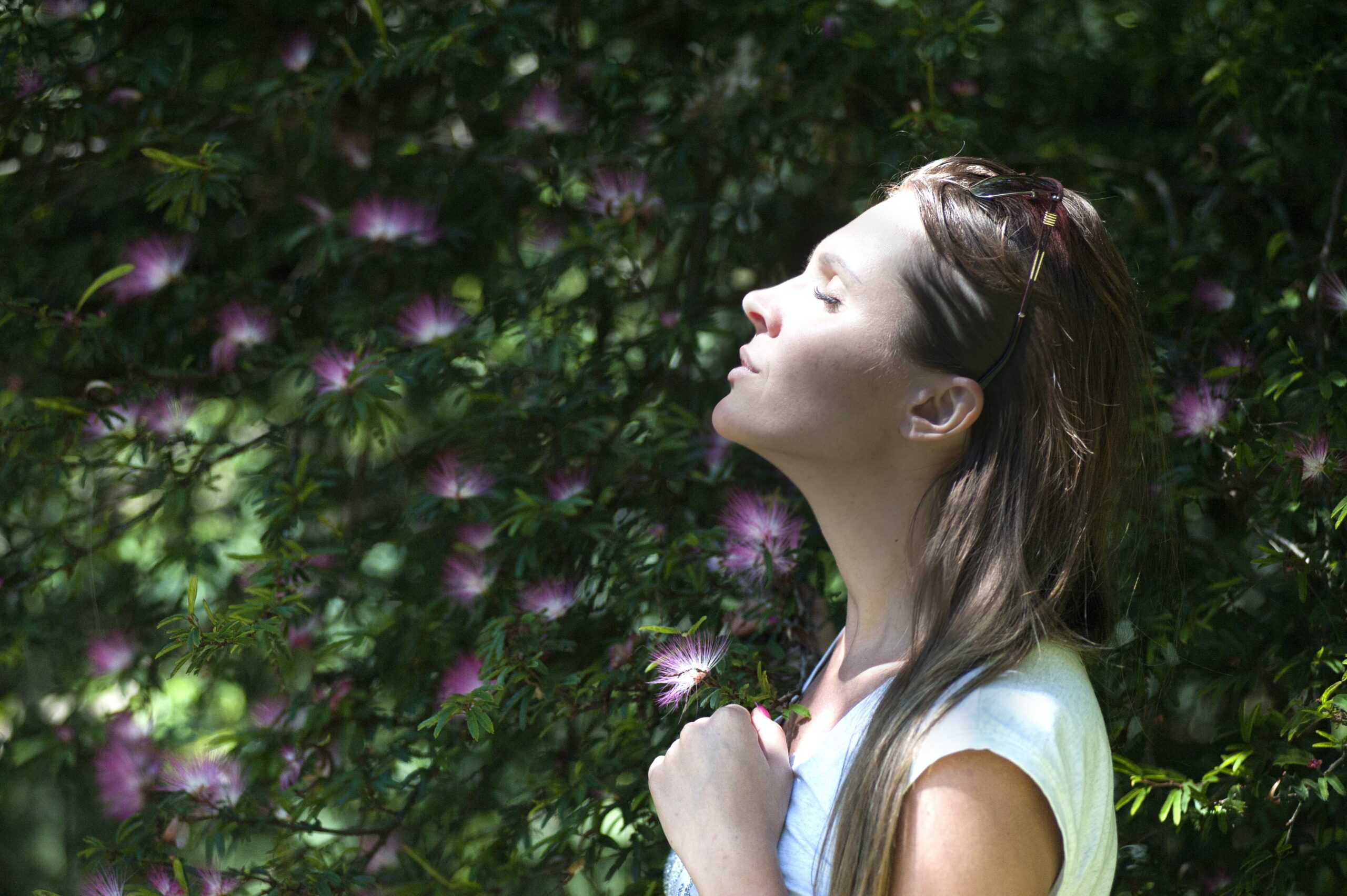 woman praying while standing in trees. She has her hands clasped in front of her while eyes are closed and head leaning back facing heaven.