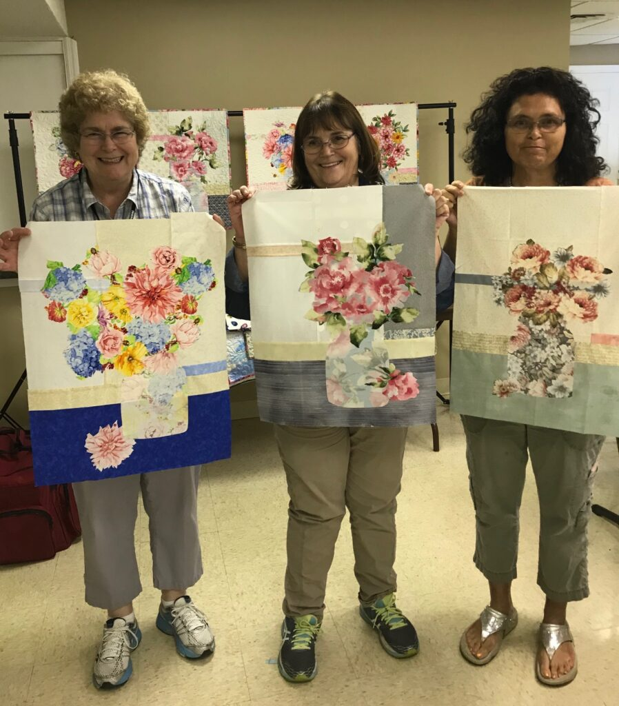 Image of Three Quilters with Quilts