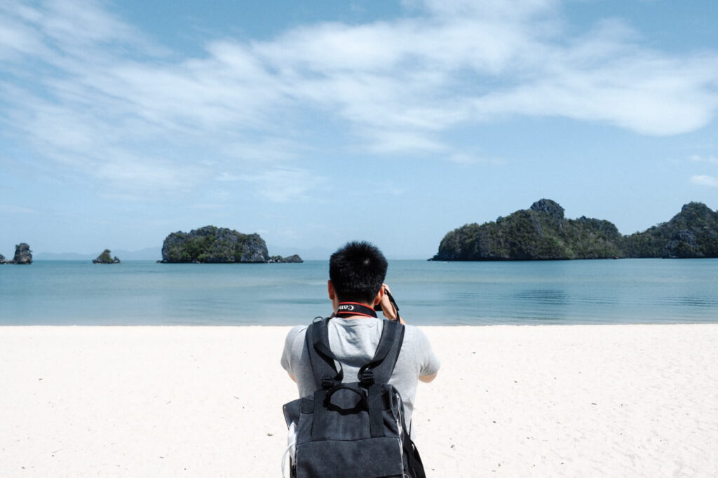 Man taking photograph on a white sandy beach