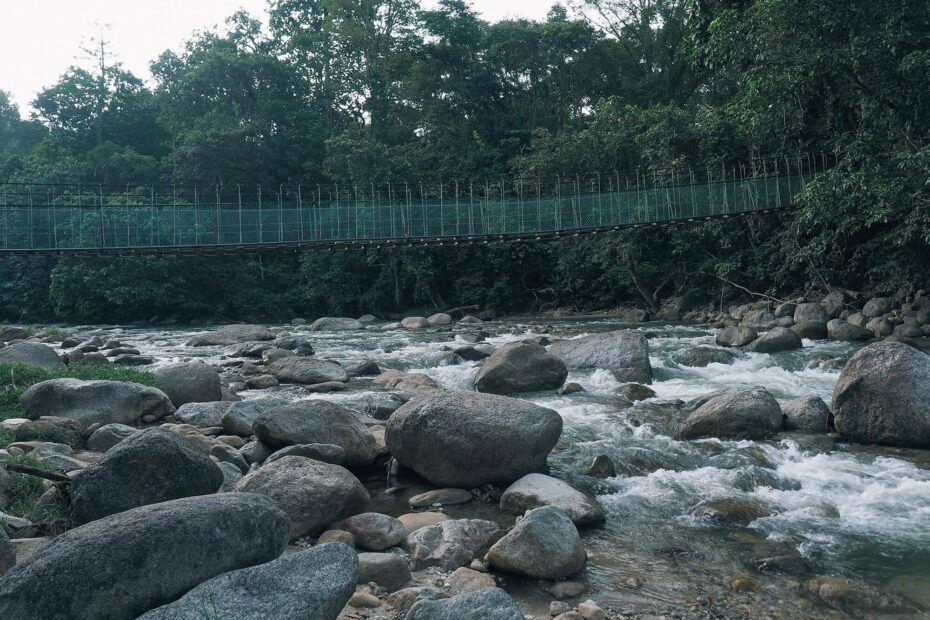 Suspension bridge over a rocky and wide river