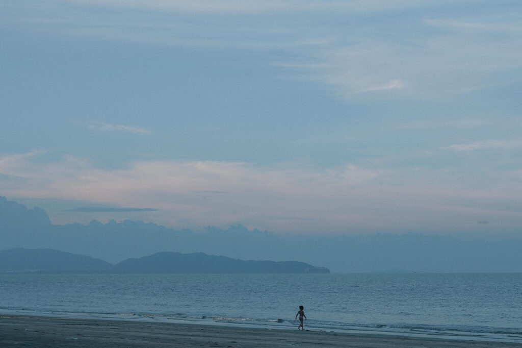 A walking child silhouette beside the beach at sunset