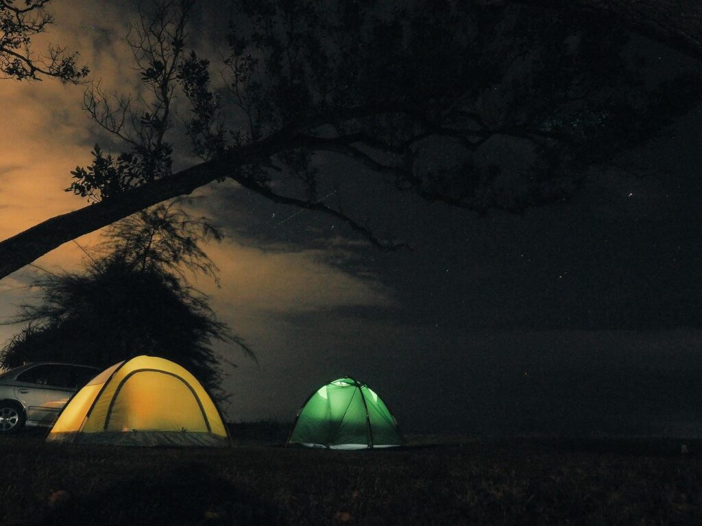 Two tents lit up at night beside the beach