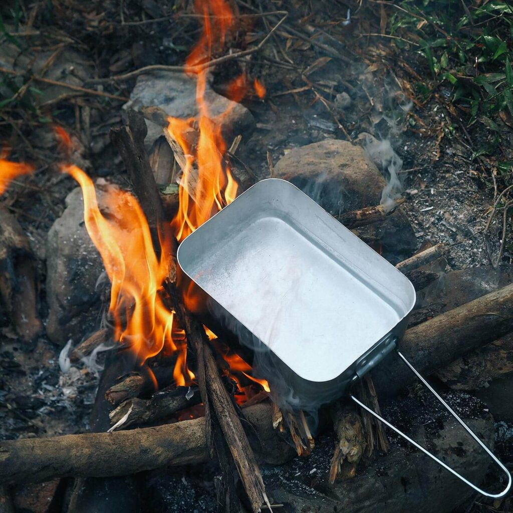 Boiling water with a mess tin on campfire
