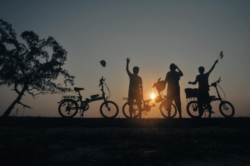 Three cyclist posing with their bicycle enjoying the sunset
