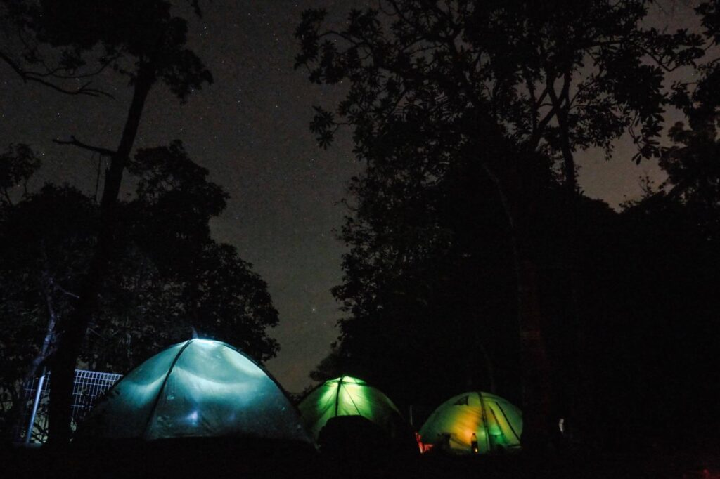 3 tents lit up under the night sky