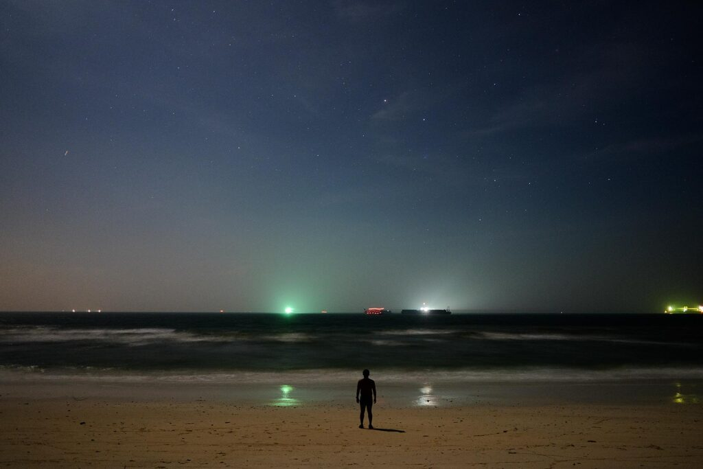 Silhouette of a man standing on the beach with night sky full of stars