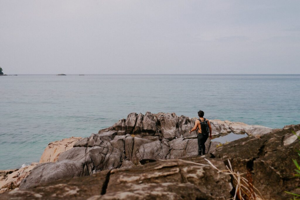 Man walking on the rock overseeing the sea