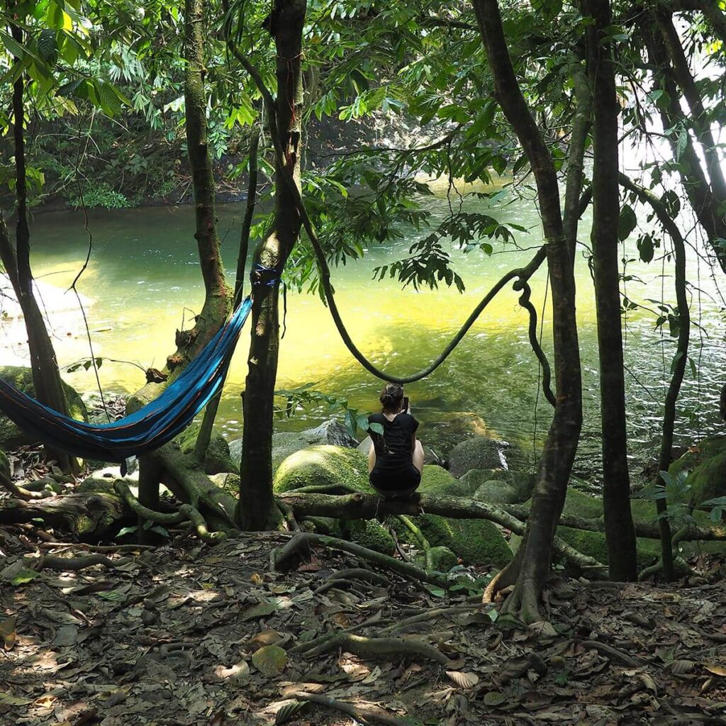 Girl squatting beside a hammock looking at the waterfall