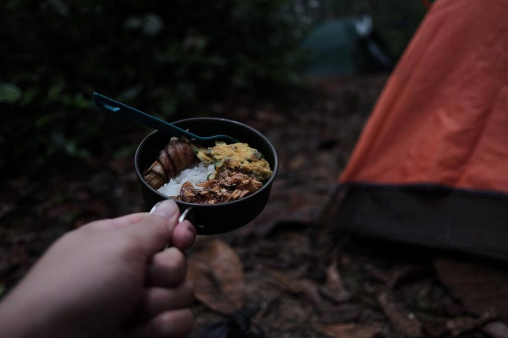 Hand posing with a camping meal