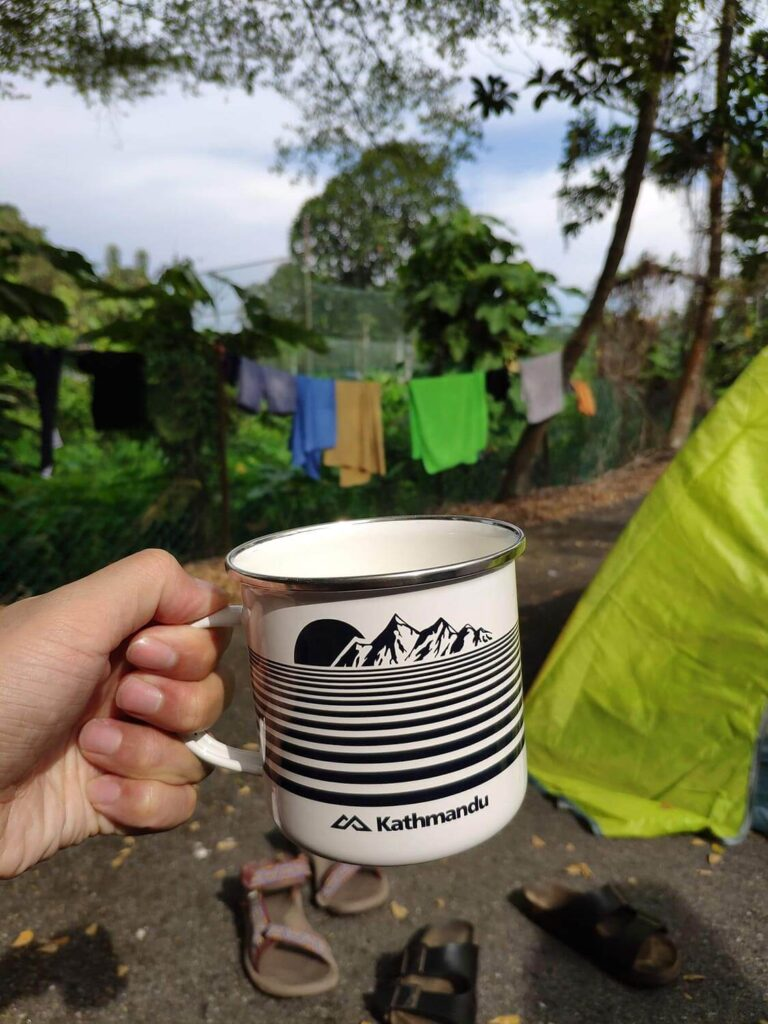 Hand holding a mug in front of the tent
