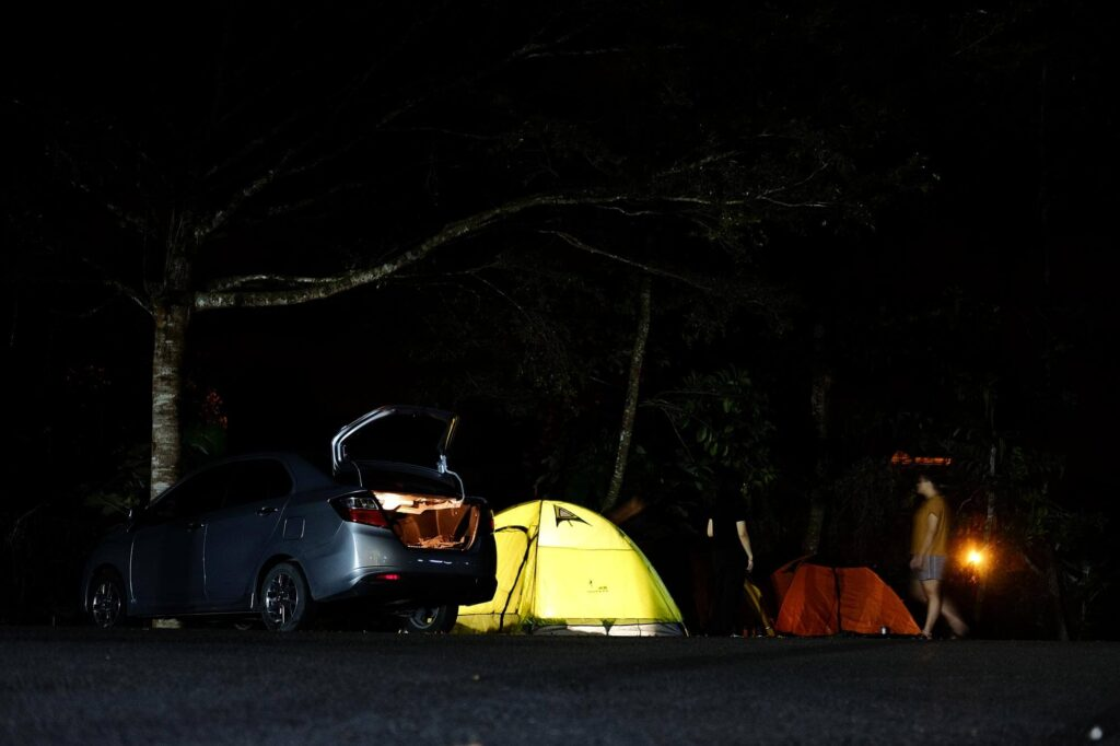 3 tents lit up beside the car