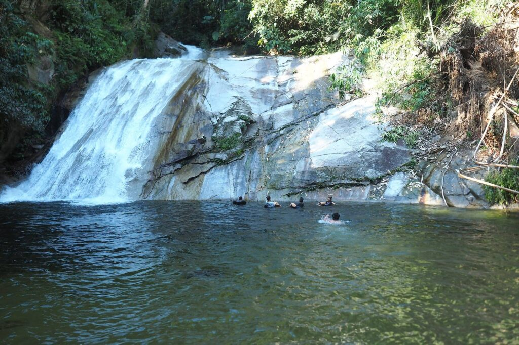 Few people swimming in big pool in front of the waterfall