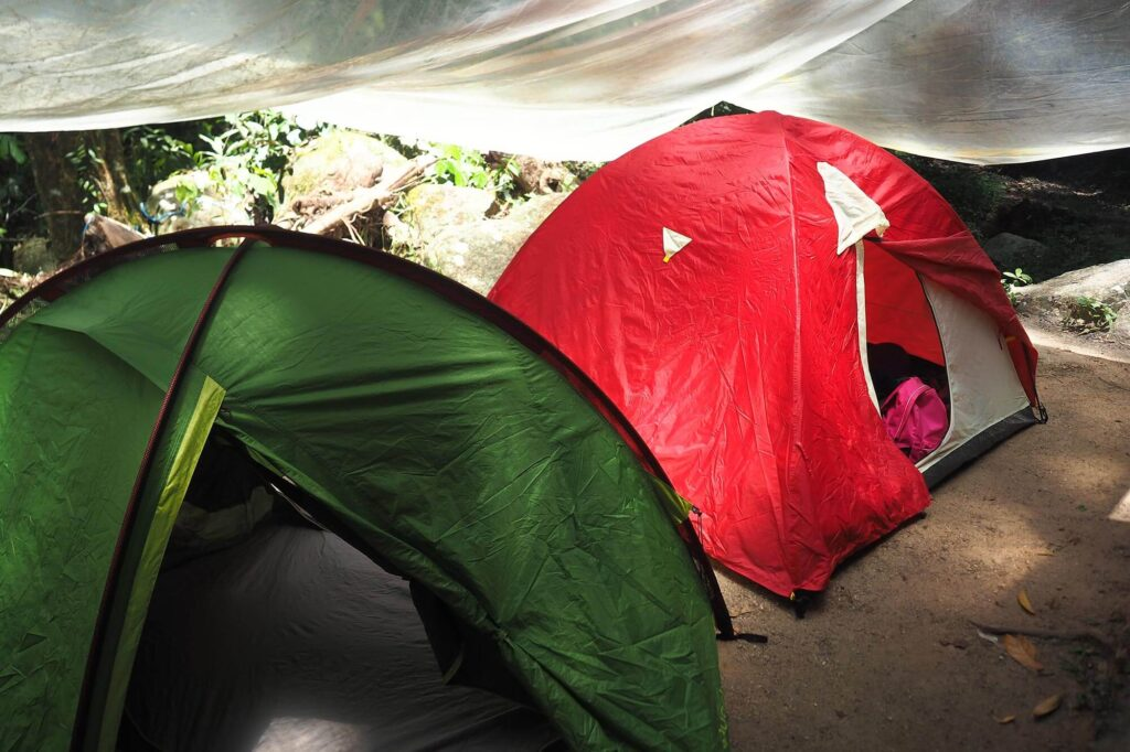 Green and red tent set up under a transparent shade