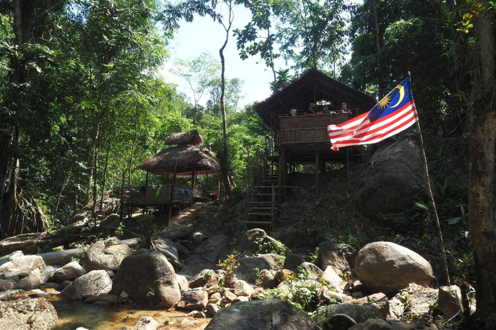 A Malaysian flag in front of a few bamboo huts