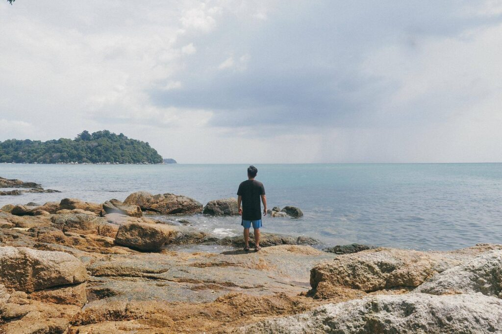 A man standing on the rock, looking at the opposite island
