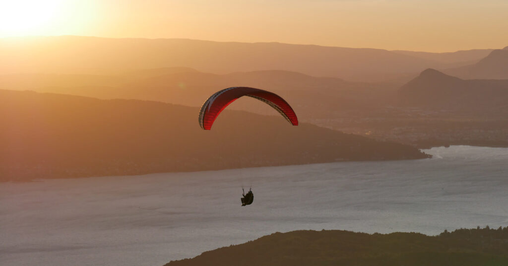 A paraglider flying over a river