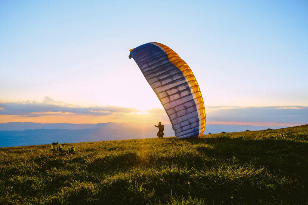 A paraglider preparing to take off at the edge of a mountain