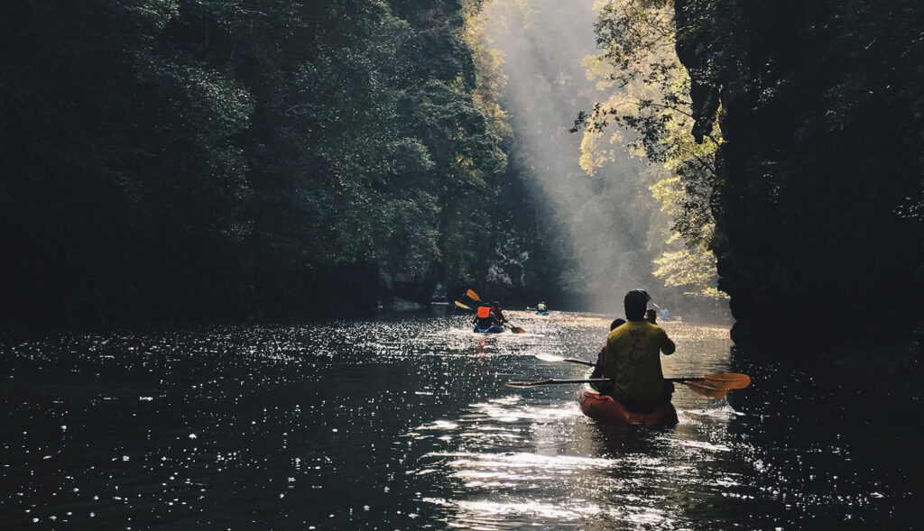 2 kayaks on the river with light ray shining down the river