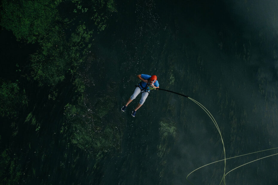 A man hanging on a rope swinging