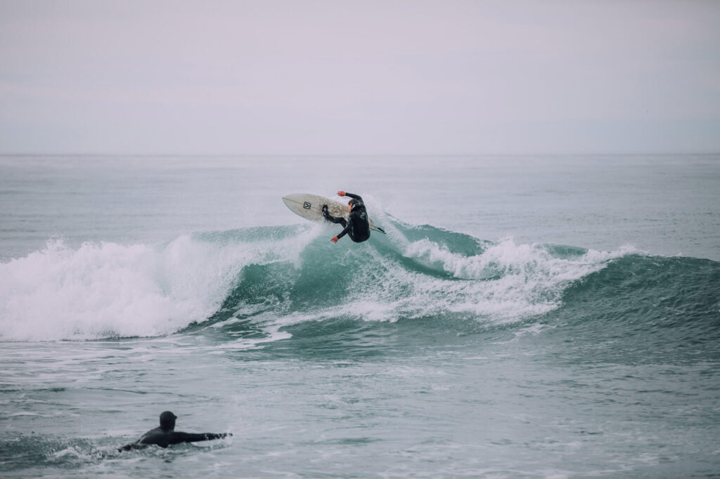 A man doing surf stunts on a wave