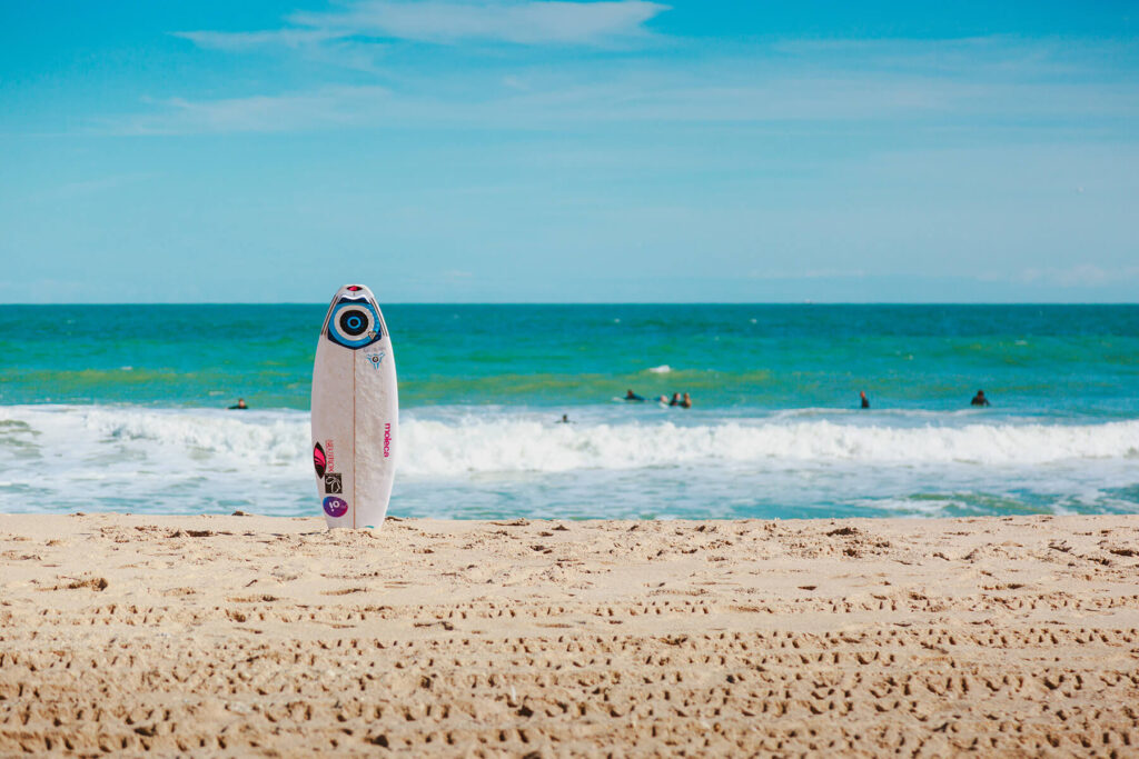 A surfboard placed vertically at the beach