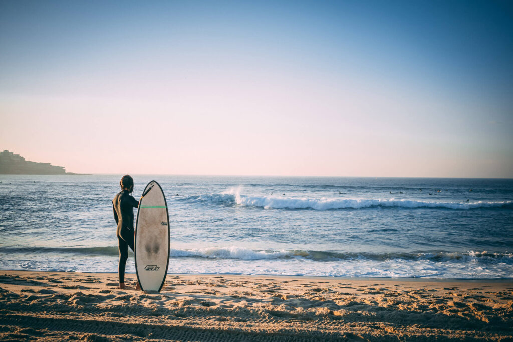 Surfer standing with a surfboard at the beach