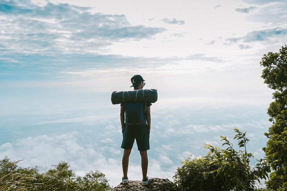 man in black shirt standing on cliff facing sea of clouds photo
