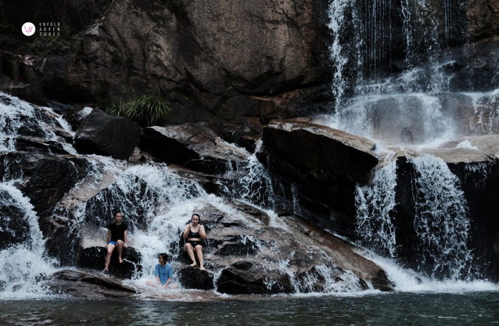 3 friends sitting on the rock under the waterfall