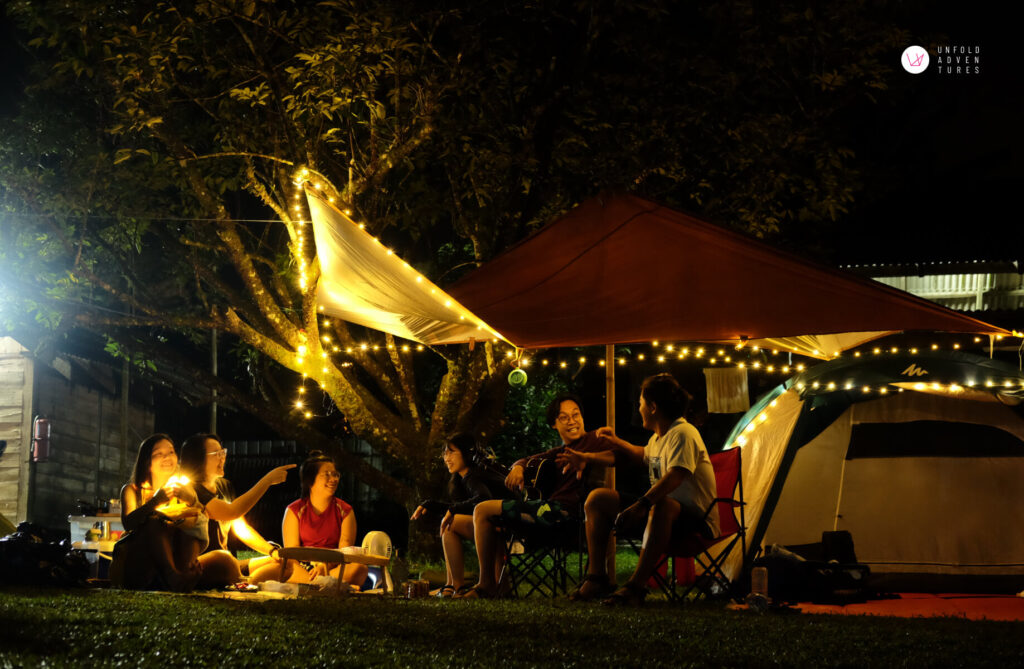 group of friends having fun under the canopy at night