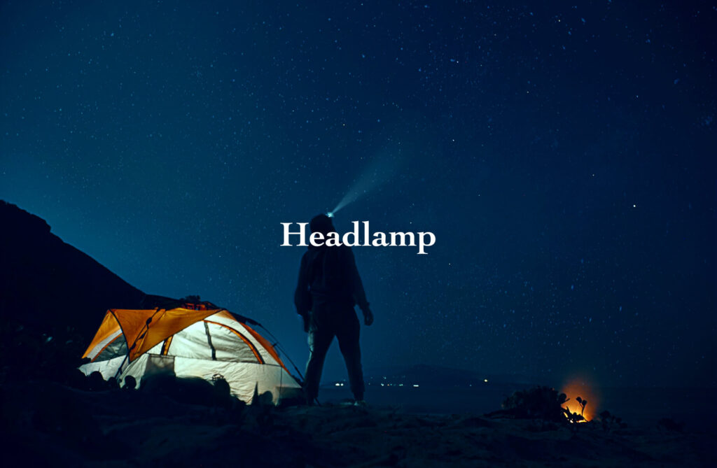 man with headlamp posing in front of the tent at night