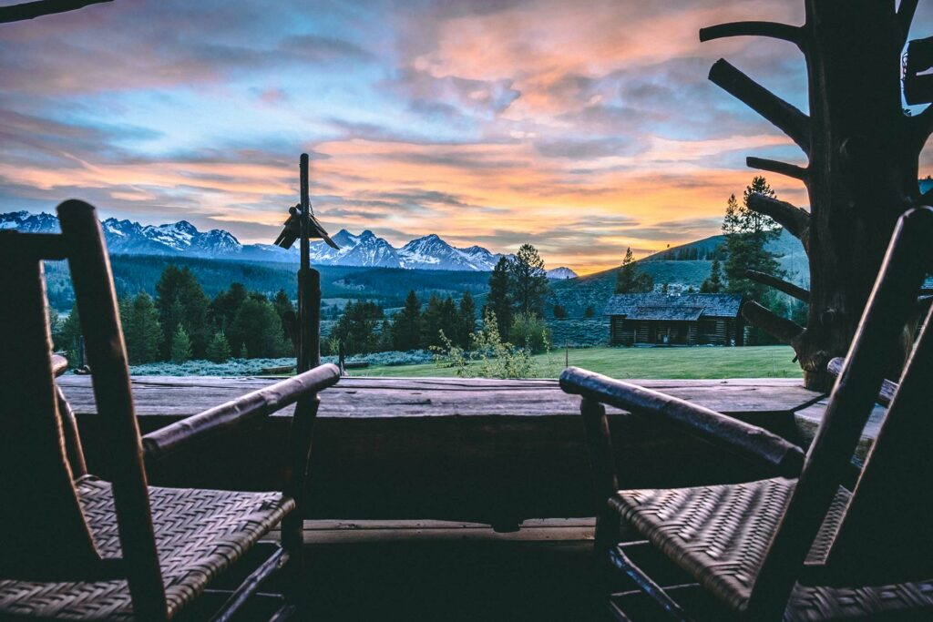 Watching the sun set behind the sawtooth mountains from the cozy porch of a log cabin at a luxury resort