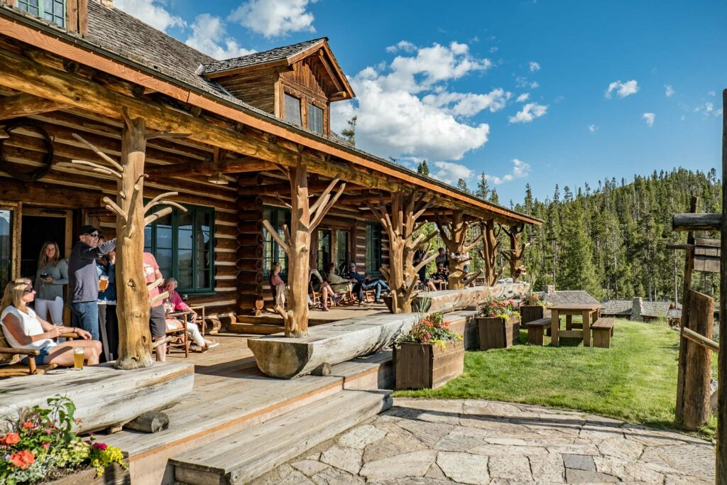 Hanging with family and friends on the porch of a log lodge at a rocky mountain ranch