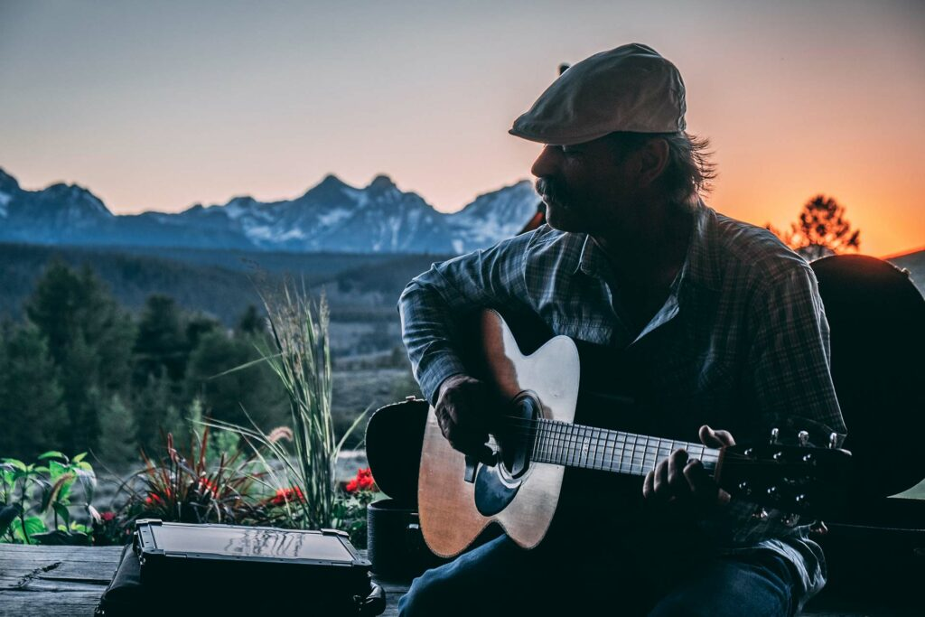A relaxing time playing a guitar as the sun sets behind the sawtooth mountains on the porch of a log cabin at an idaho guest resort