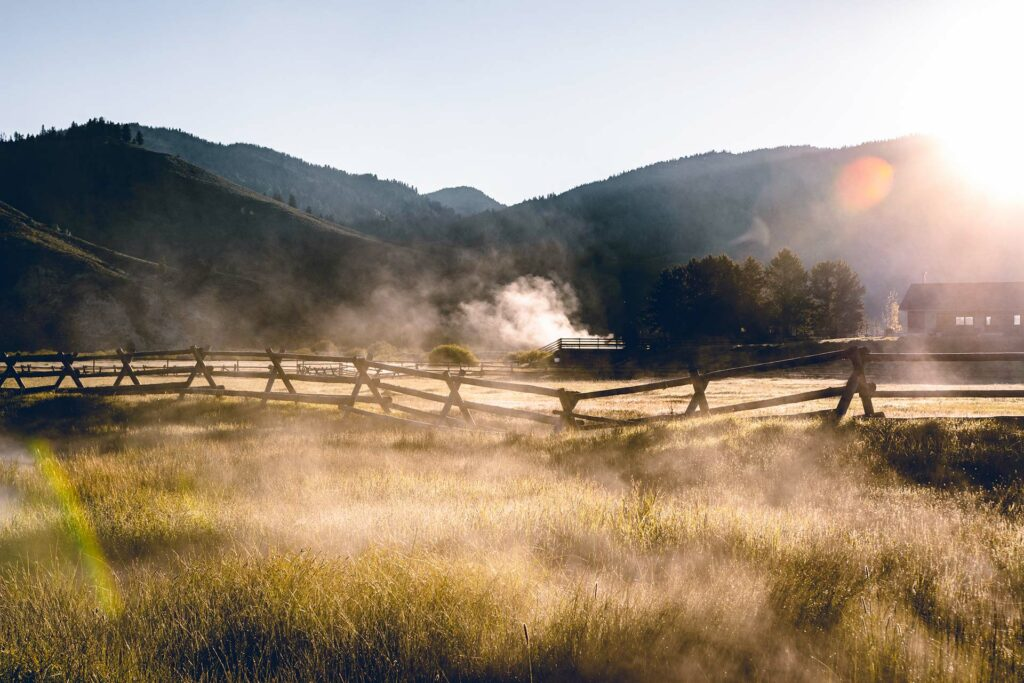 Steam rising on a beautiful morning at the Idaho Rocky Mountain Ranch in a green valley at the base of the rocky mountains