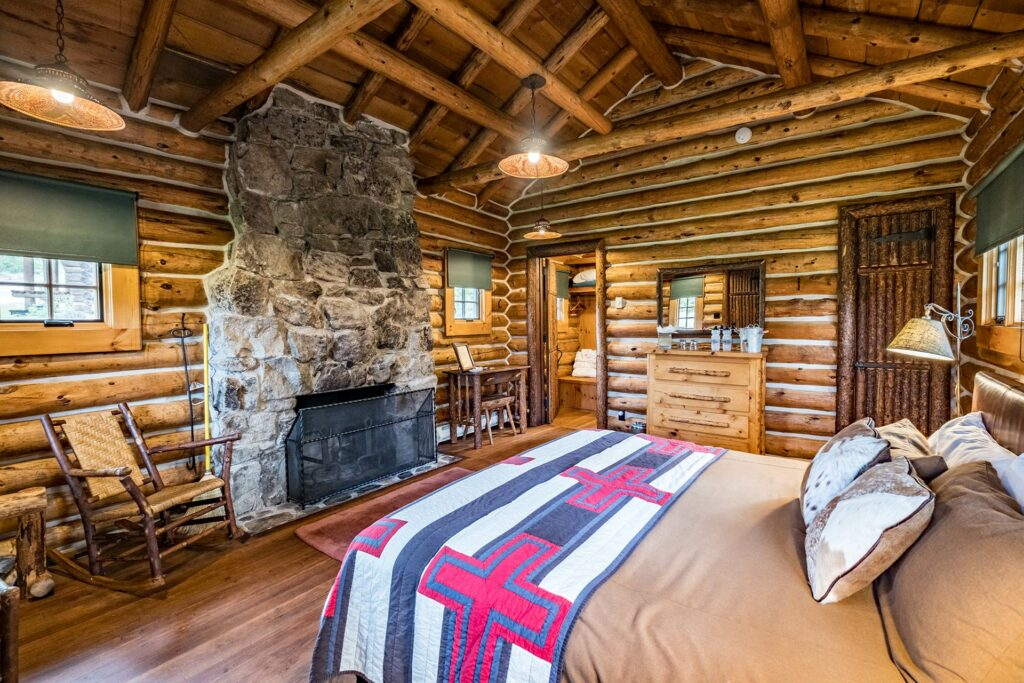A cozy master bedroom including a fire place and private bathroom in our guest log cabin in stanley idaho