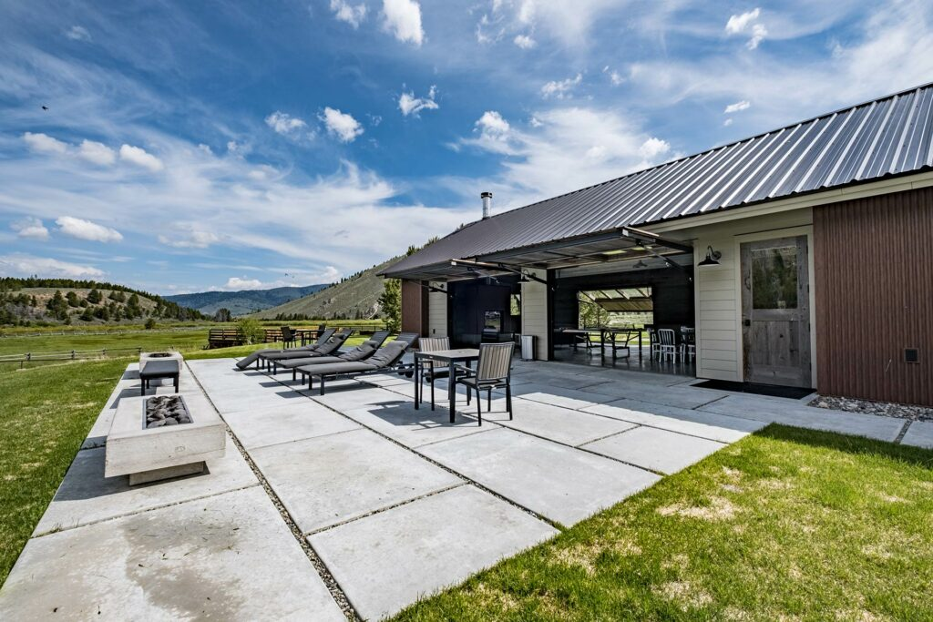 An overhead view of the idaho rocky mountain ranch lodge with our private rocky mountain hot springs in a beautiful green valley and big open blue sky with lounge seats