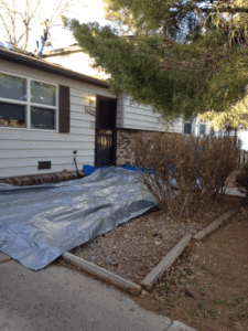 Tarp being used outside a home to protect the ground from roofing damage