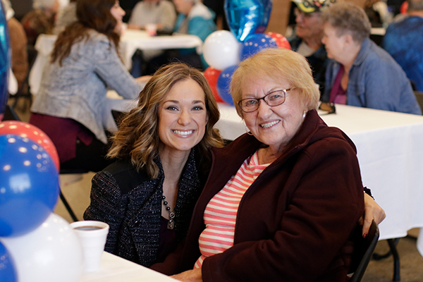young woman and elderly woman at a luncheon
