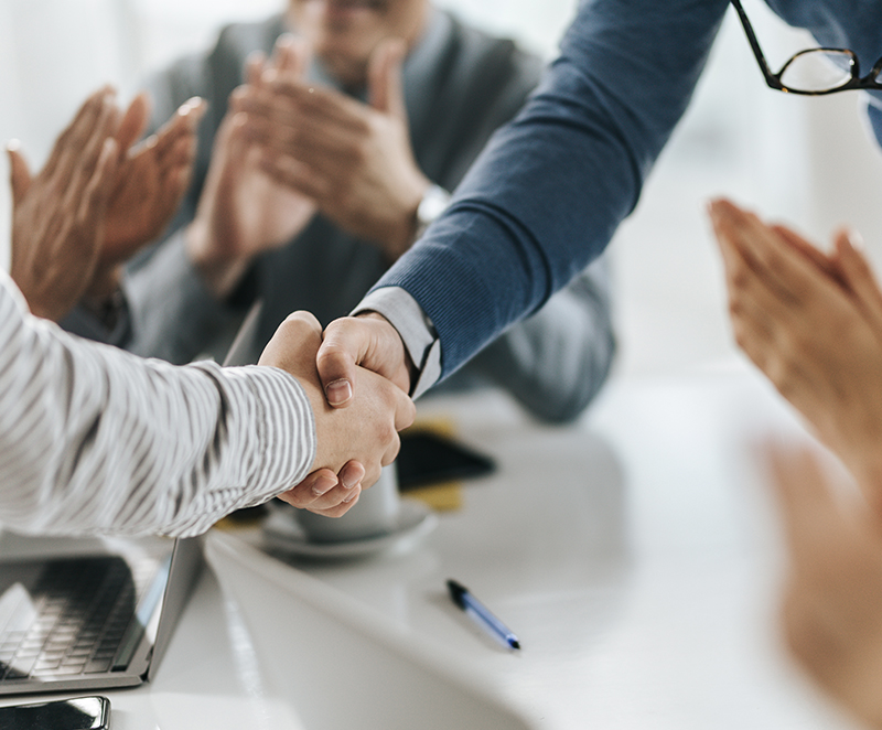 Two people shaking hands while others are clapping