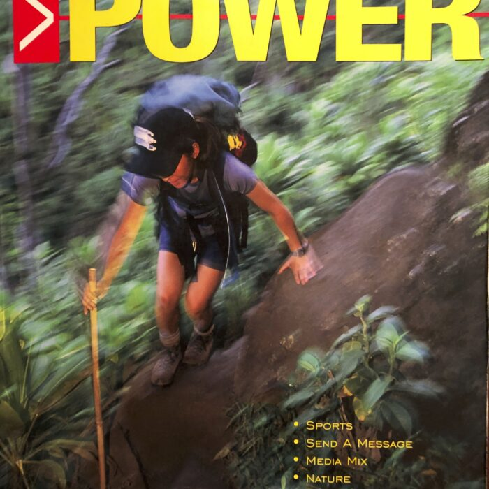 Cover of the book Literacy Power. A person is climbing over some large rocks in a forest. The person is wearing hiking boots, shorts, a tshirt, a baseball cap and is carrying a large hiking pack.