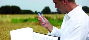 Man holding clipboard in left hand and test tube in right, doing work outside in a field